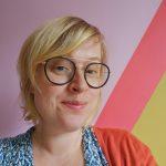 Tevreden lachende blonde Corina met dikke zwarte bril en kleurige kleding tegen een muur van roze en mostergeel met een dikke felroze streep in het midden