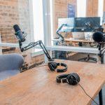 setup voor een podcast een bureau van hout met een grijze bureaustoel en twee microfoons