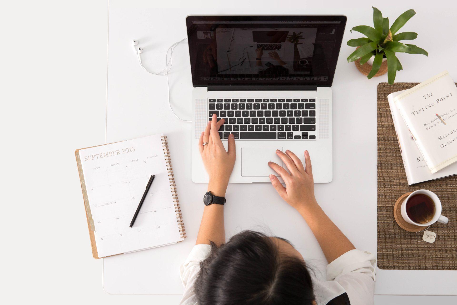 vrouw van bovenaf gezien werkt aan laptop, naast haar een blok met pen door Avel Chuklanov via Unsplash