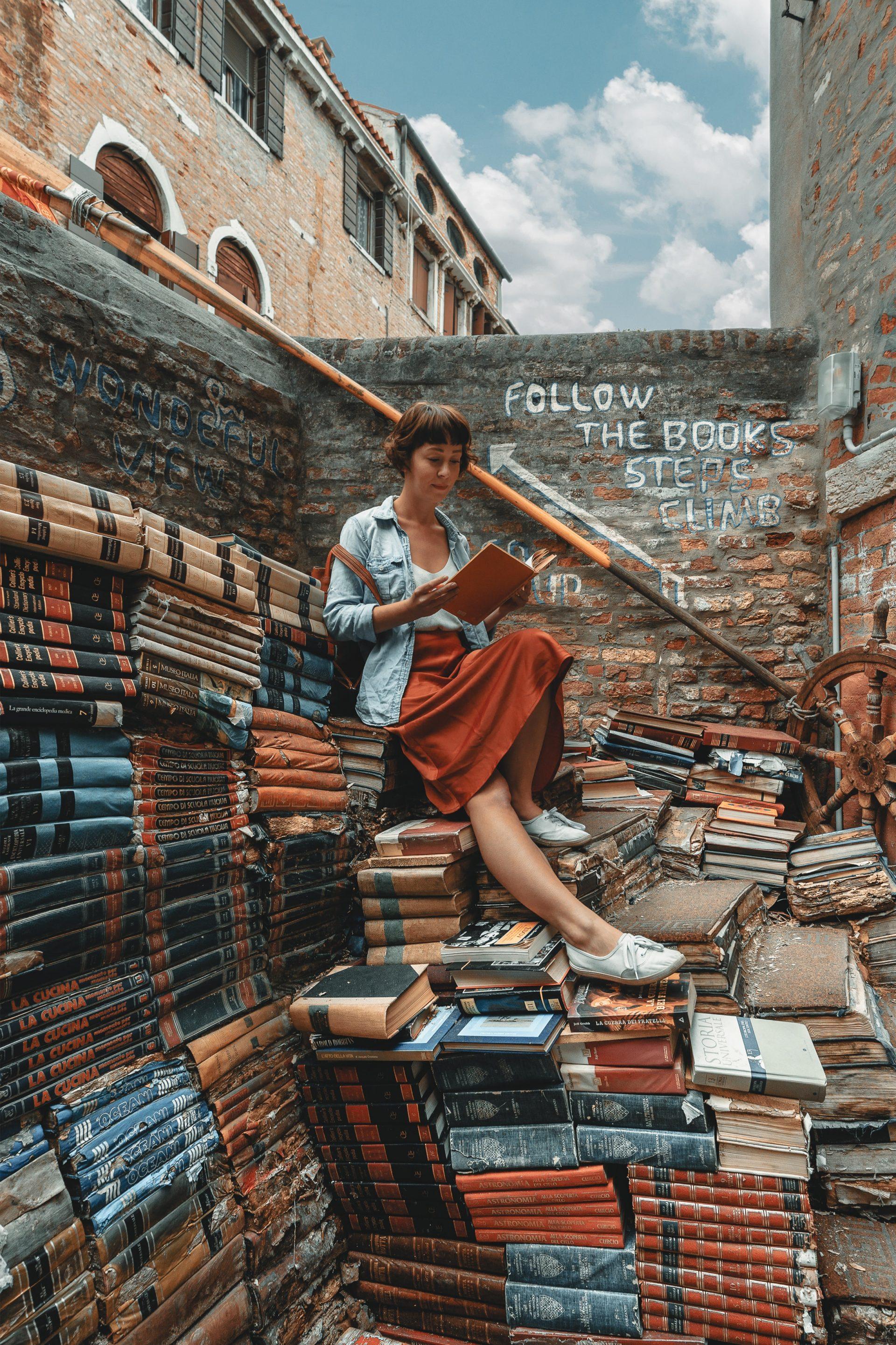 Vrouw leest een boek op een stapel boeken in de vorm van een trap door Clay Banks via Unsplash