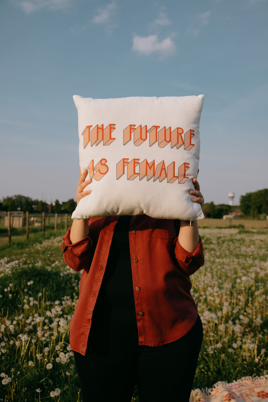 Dikke vrouw houdt kussen vvoor haar hoofd met de tekst The future is female