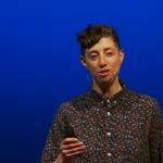 Screenshot van Emilie Wapnick tijdens haar Tedtalk. Kort krullend haar, bloes met drukke print dichtgenkoopt tot haar nek. Clicker in de hand. Blauwe achtergrond.