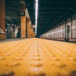 Een metroplatform gezien vanaf de grond, het beeld wordt gevuld met een gele blindegeleidenstrook. Je oog wordt getrokken naar het doel, het einde van de streep. Credit: Martin Sanchez via Unsplash